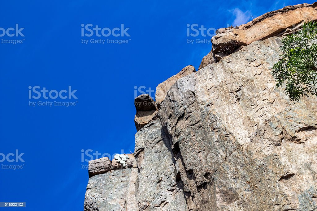 Up view of steep rock cliff stock photo