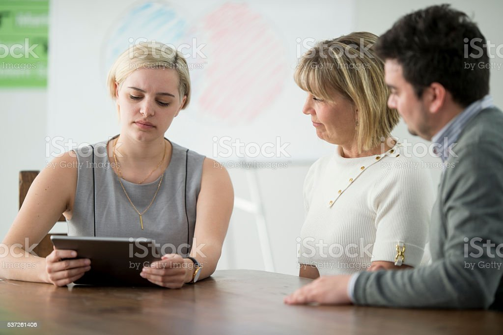 A group of business professionals are looking at their online...