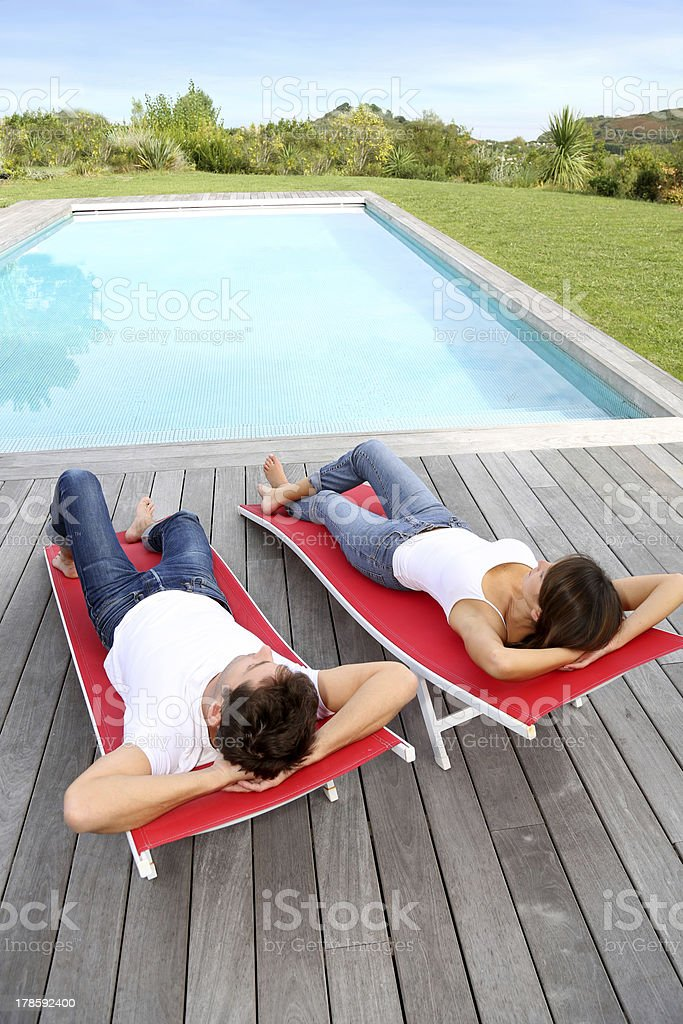 Upper view of couple in long chairs by side pool royalty-free stock photo