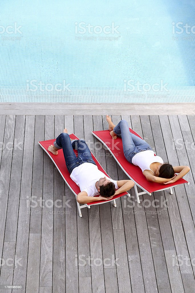 Upper view of couple sitting in red deck chairsby pool stock photo