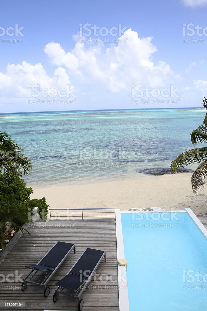 Upper view of smwimming-pool and long chairs by the sea royalty-free stock photo
