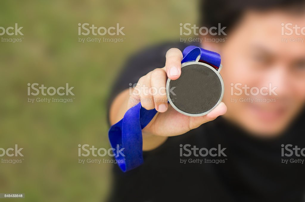 Uprisen Angle Of Asian Athlete Holding Generic Gold Medal. stock photo