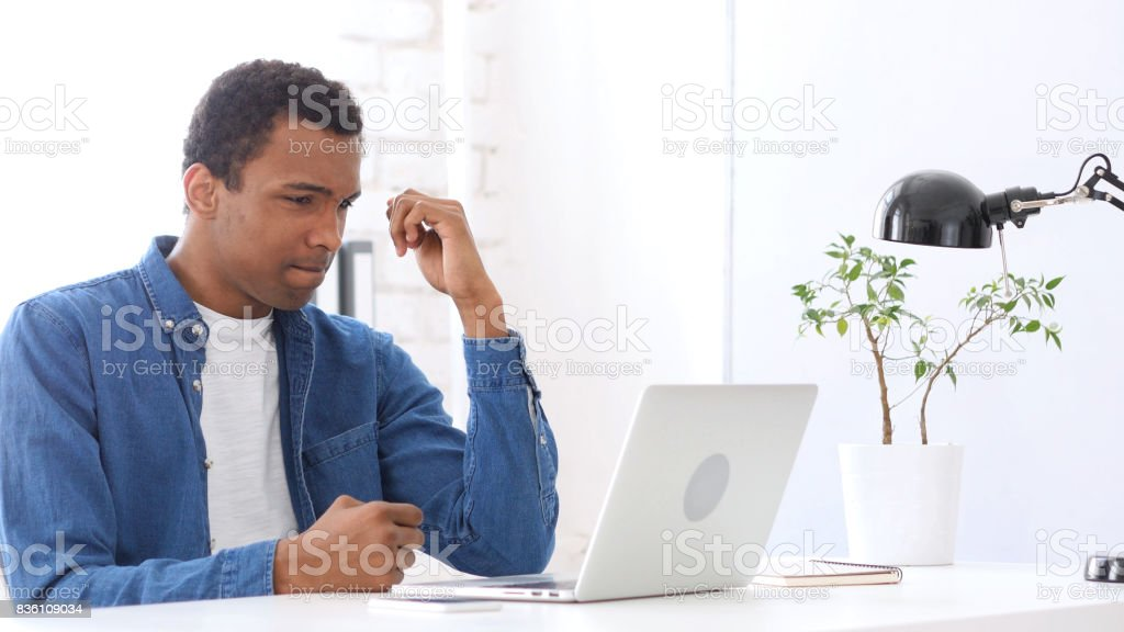 Upset Afro-American Man at Work, Looking at Laptop stock photo