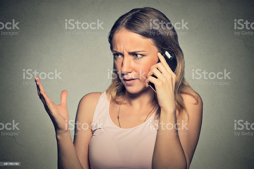 upset angry skeptical, unhappy, serious woman talking on mobile phone stock photo