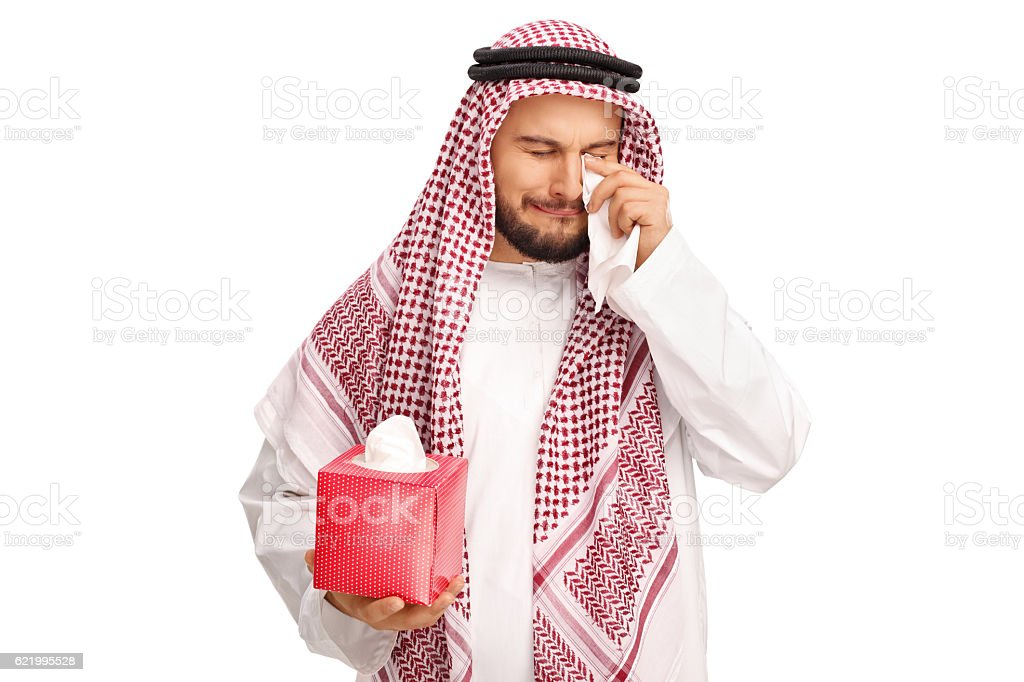 Upset Arabian man crying and wiping his tears with napkins stock photo