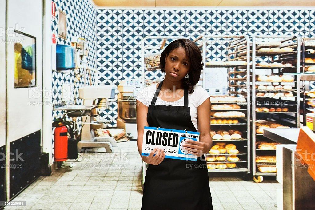 Upset baker holding closed sign in bakery stock photo