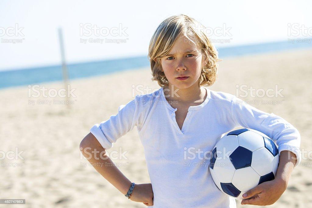 En colère garçon tenant un ballon de football en plein air. photo libre de droits