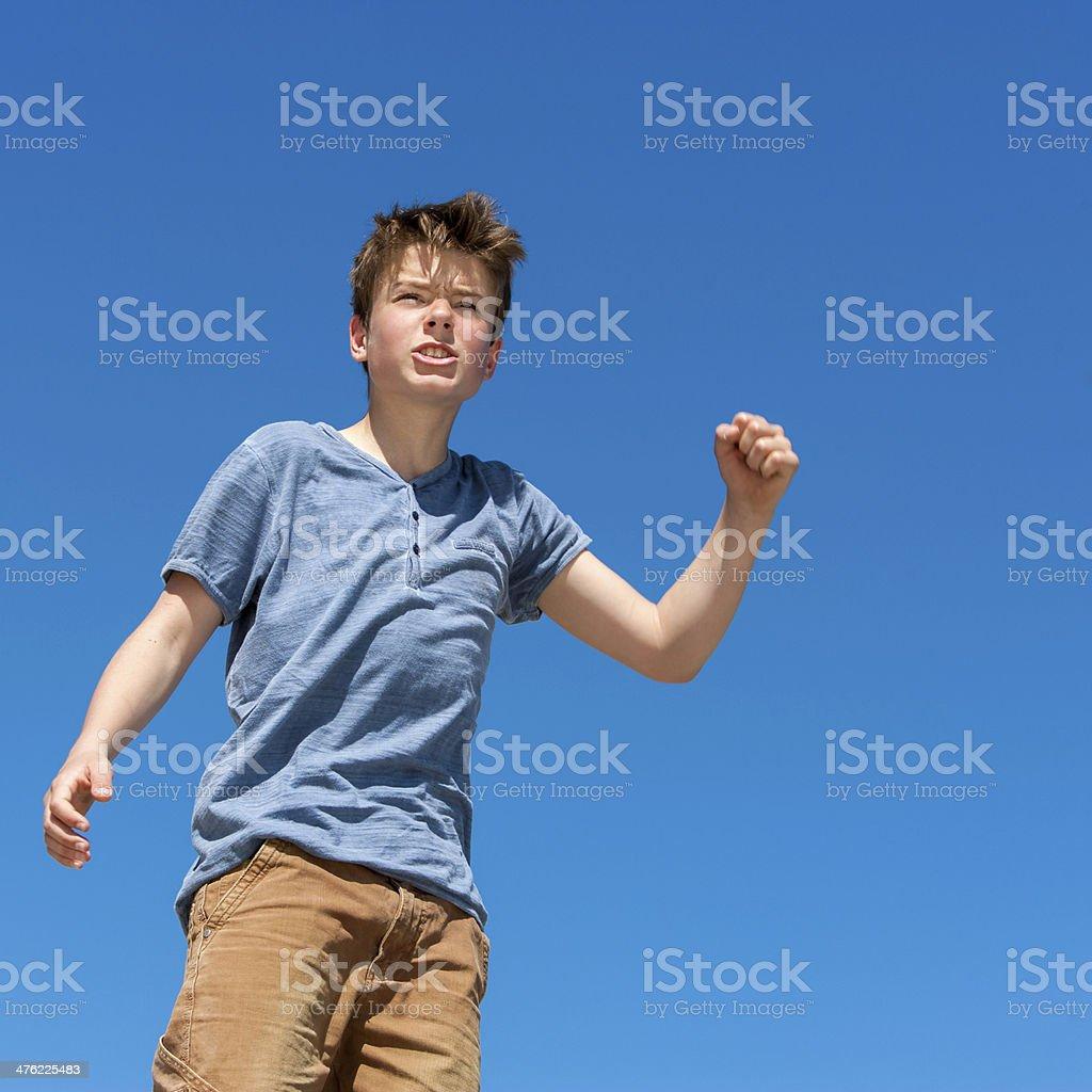 Upset boy raising fist outdoors. royalty-free stock photo