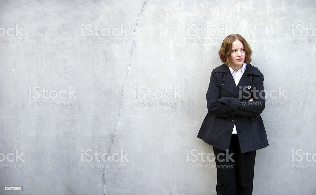 Upset Brunette Woman Leaning on Concrete Wall royalty-free stock photo