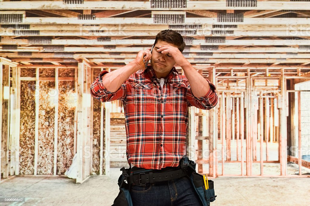 Upset building contractor on phone stock photo