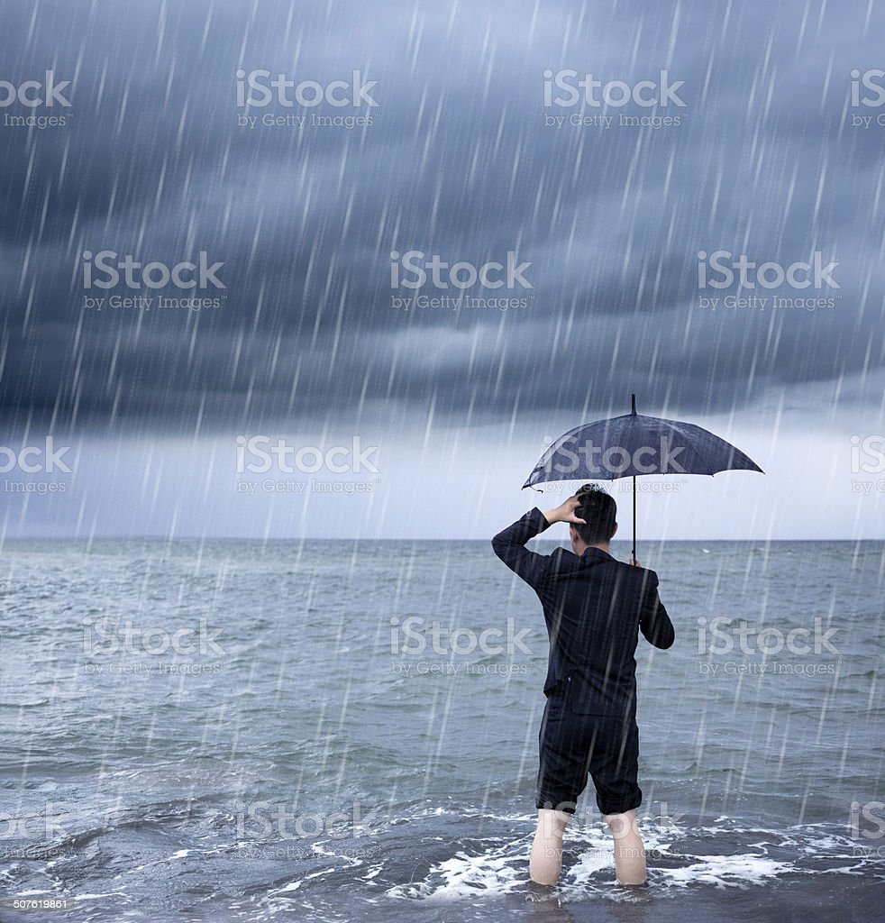 upset business man holding a umbrella with cloudburst background stock photo