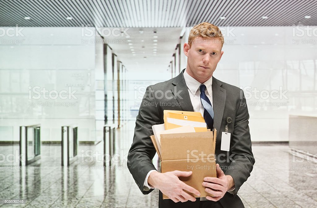 Upset businessman holding box in office stock photo