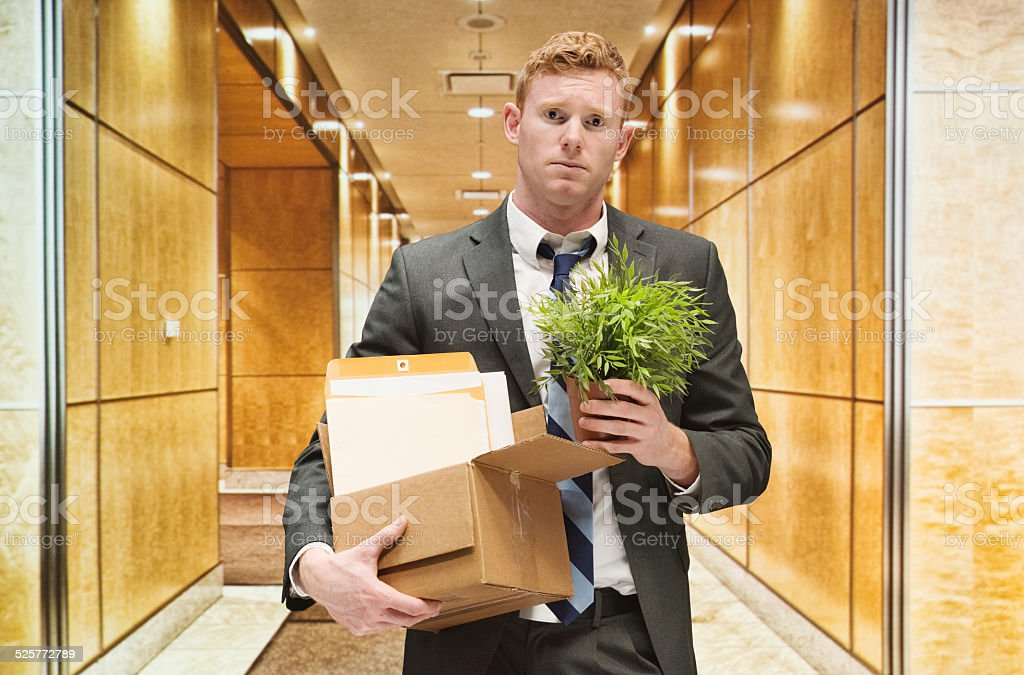 Upset businessman holding box in the...