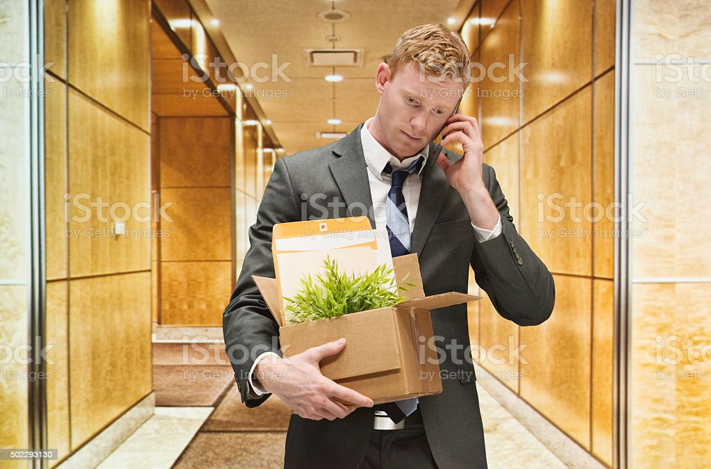 Upset businessman on mobile and fired from his job stock photo