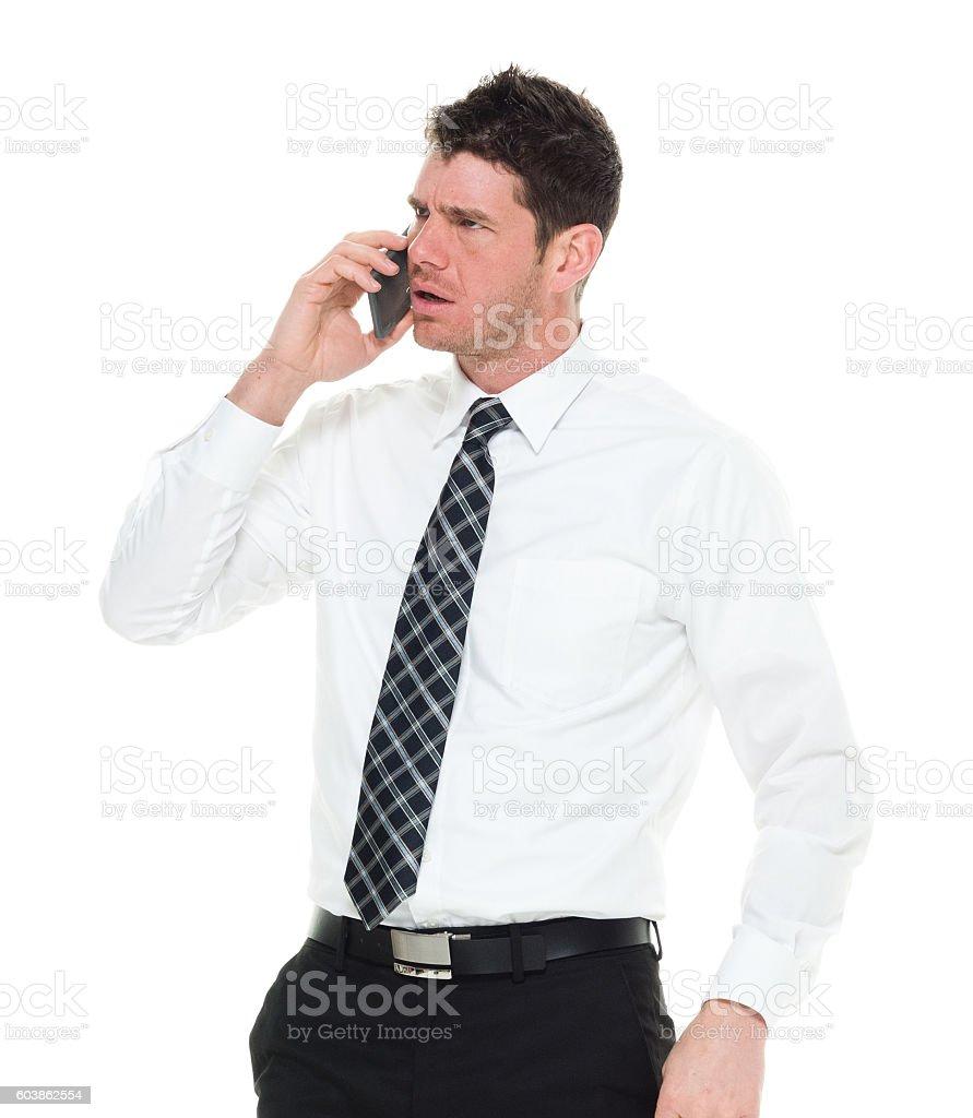 Upset businessman talking on phone stock photo