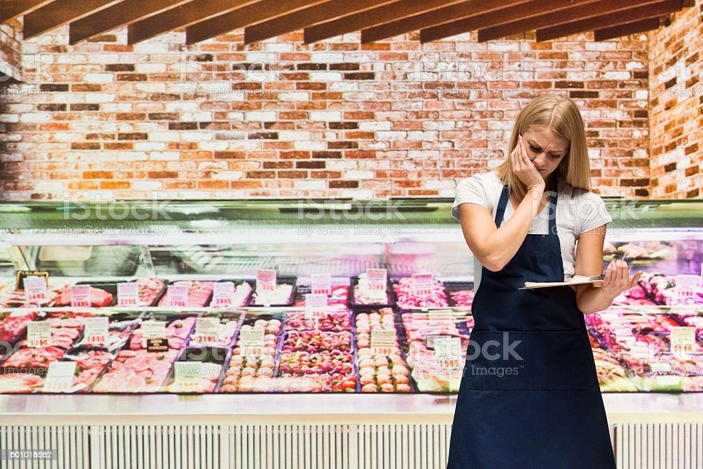 Upset butcher standing in shop stock photo