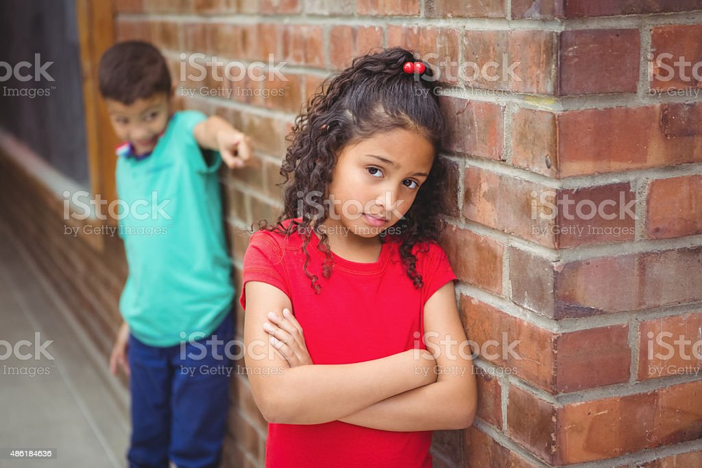 Upset child being teased at school stock photo