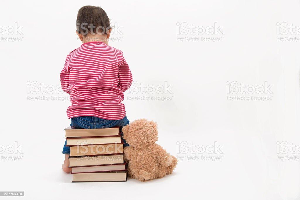 Upset child sitting on books with her teddybear stock photo
