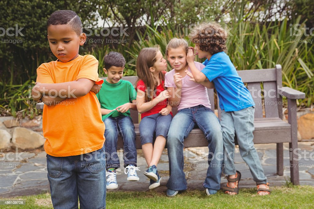 Upset child standing away from group stock photo