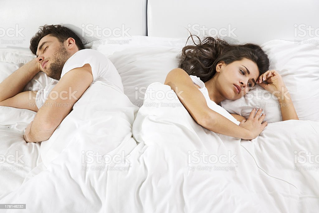 Upset couple lying  in bed stock photo