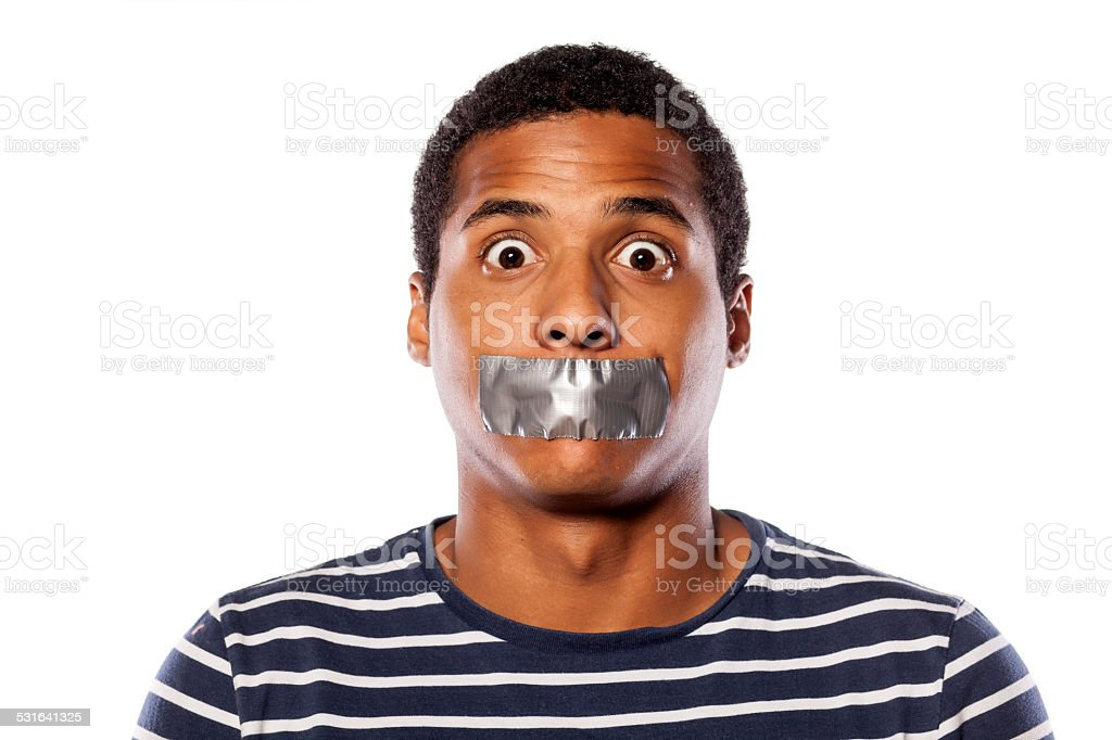 Upset dark-skinned young man with adhesive tape over his mouth stock photo