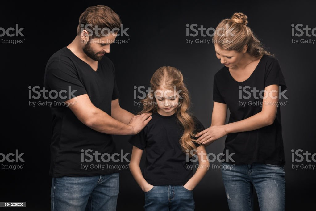 upset daughter and parents touching her and standing on black