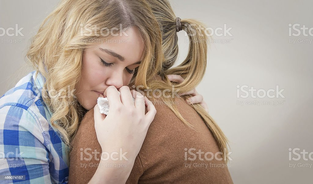 Upset daughter lays her head on mothers shoulder stock photo