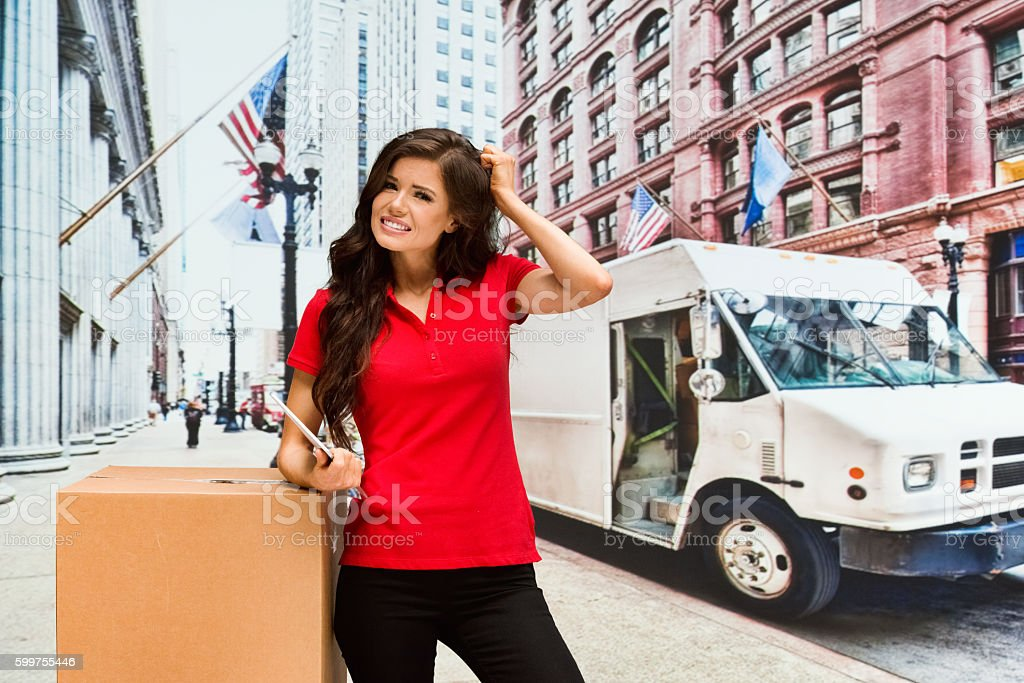 Upset delivery person pulling her hair outdoors stock photo