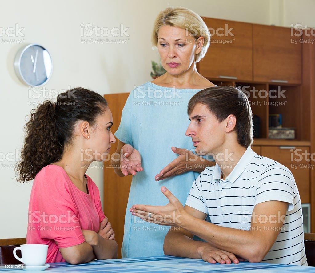 Upset female retiree watching adult kids quarrelling at home stock photo