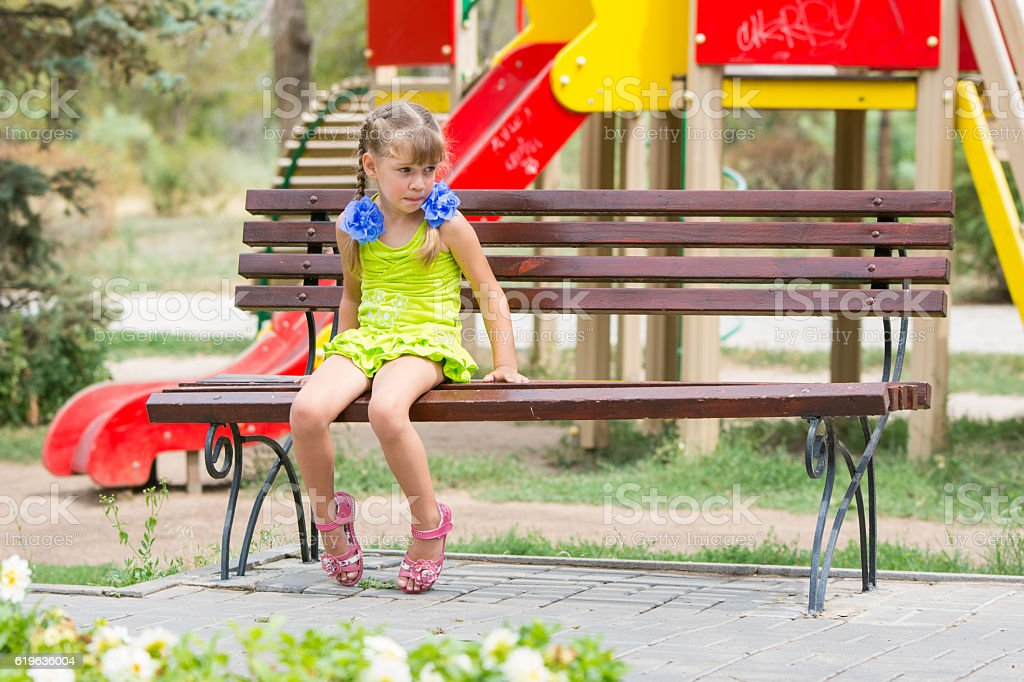 Upset girl bit her lip while sitting on the bench stock photo