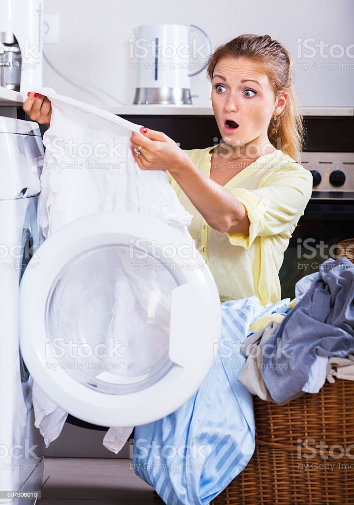 Upset girl looking at linen after laundry stock photo