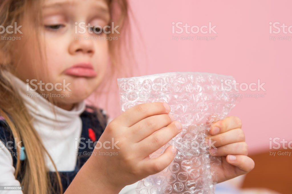Upset girl pouting cheeks eats bubbles packaging film stock photo