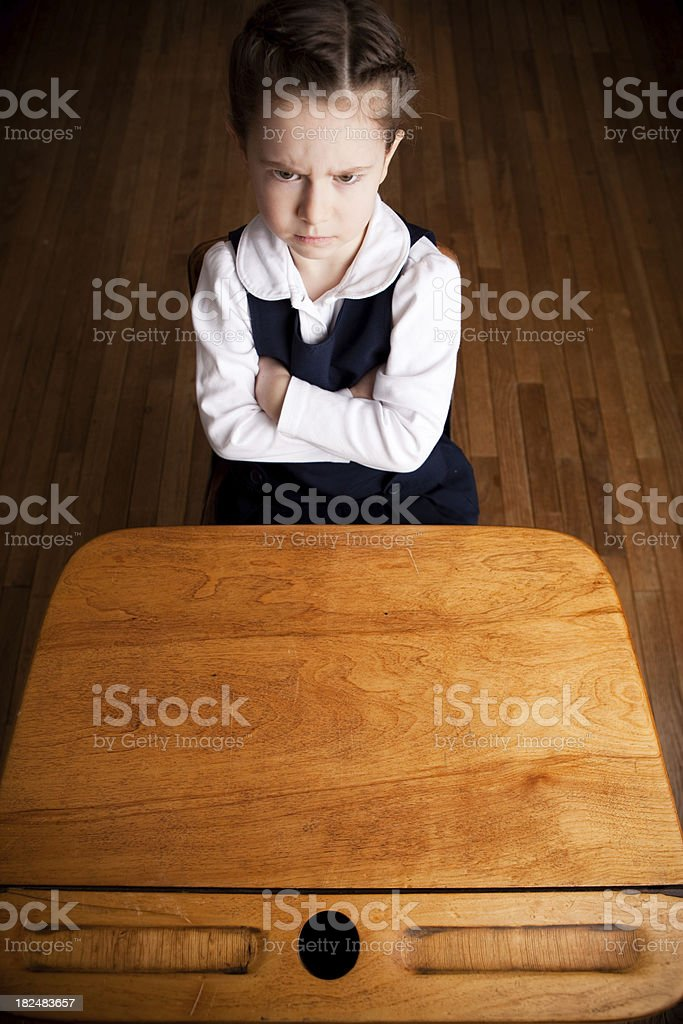 Upset Girl Student Scowling and Sitting in School Desk royalty-free stock photo