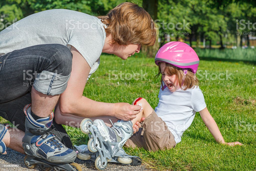 Upset girl with a knee wounded stock photo