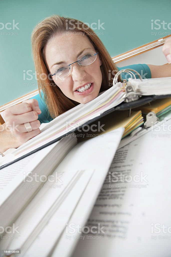 Upset Graduate Student With Piles of Class Note Binders royalty-free stock photo