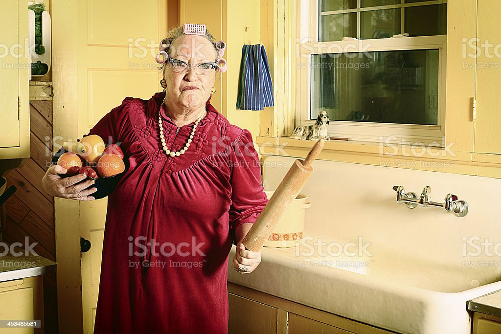 A upset grandmother standing in a kitchen holding a roller royalty-free stock photo