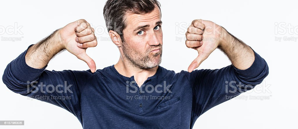 upset handsome young bearded man showing negative thumbs down stock photo
