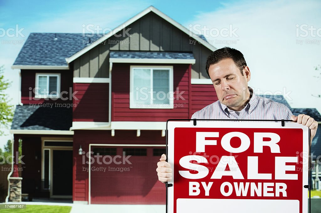 Upset home owner with 'For Sale' sign board stock photo