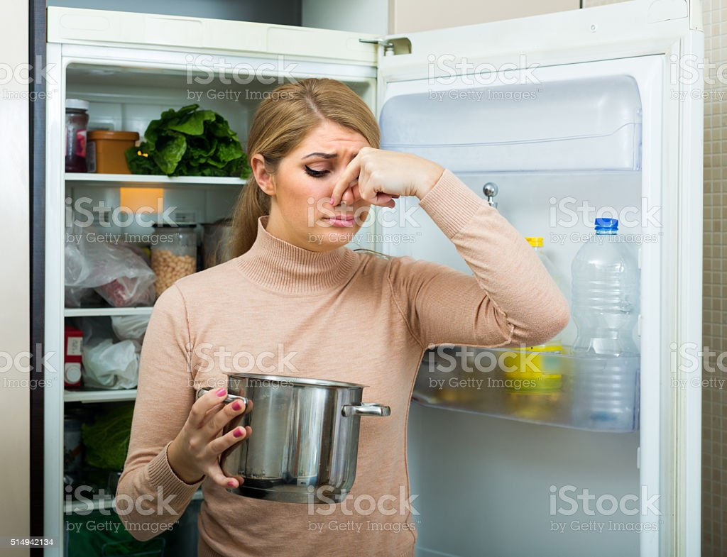 Upset housewife with foul meal stock photo