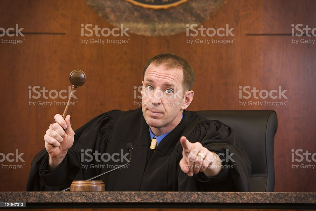 Upset judge swinging gavel and pointing royalty-free stock photo