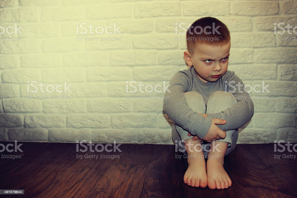Upset little boy against the wall. stock photo