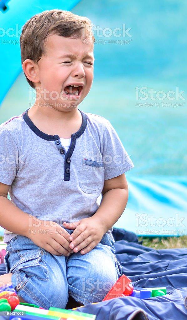 Upset little boy in the park stock photo