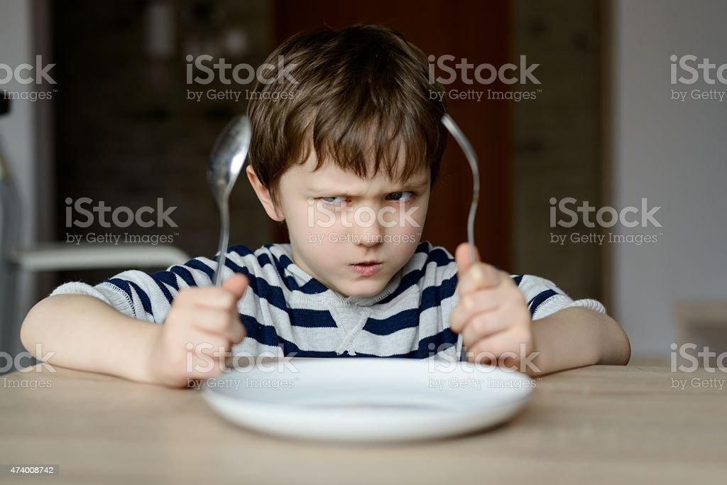 Upset little boy waiting for dinner stock photo