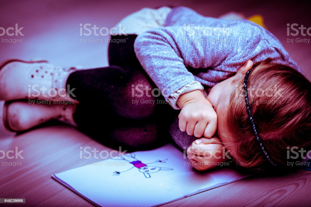 Upset little girl curled up next to her drawing stock photo