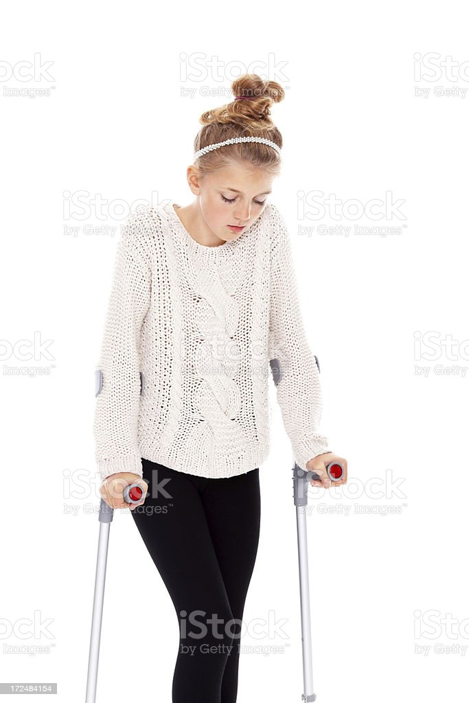 Upset little girl on crutches against white royalty-free stock photo