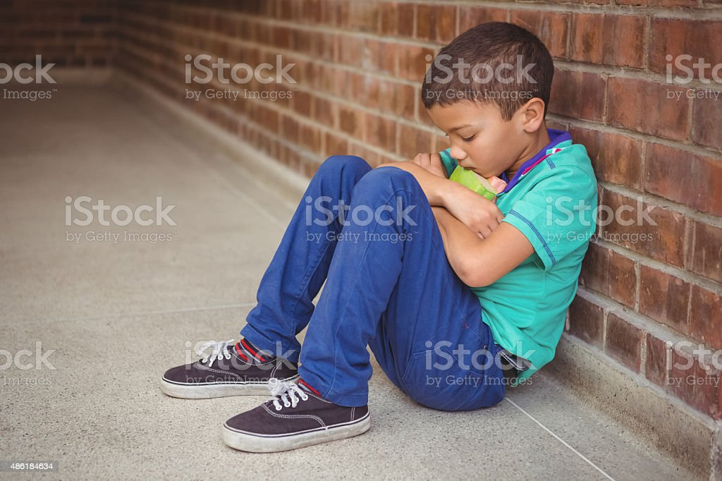 Upset lonely child sitting by himself stock photo