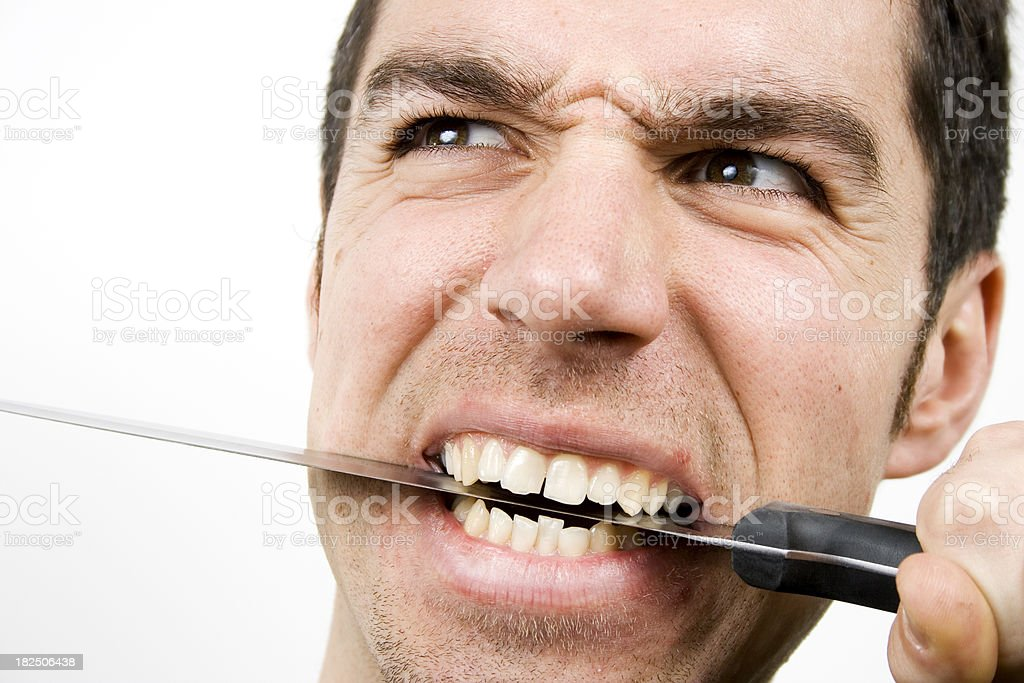 upset man gripping a knife with teeth. stock photo