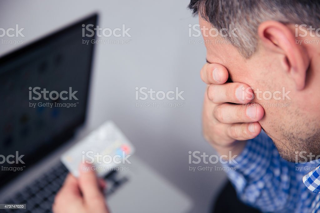 Upset man holding credit card stock photo