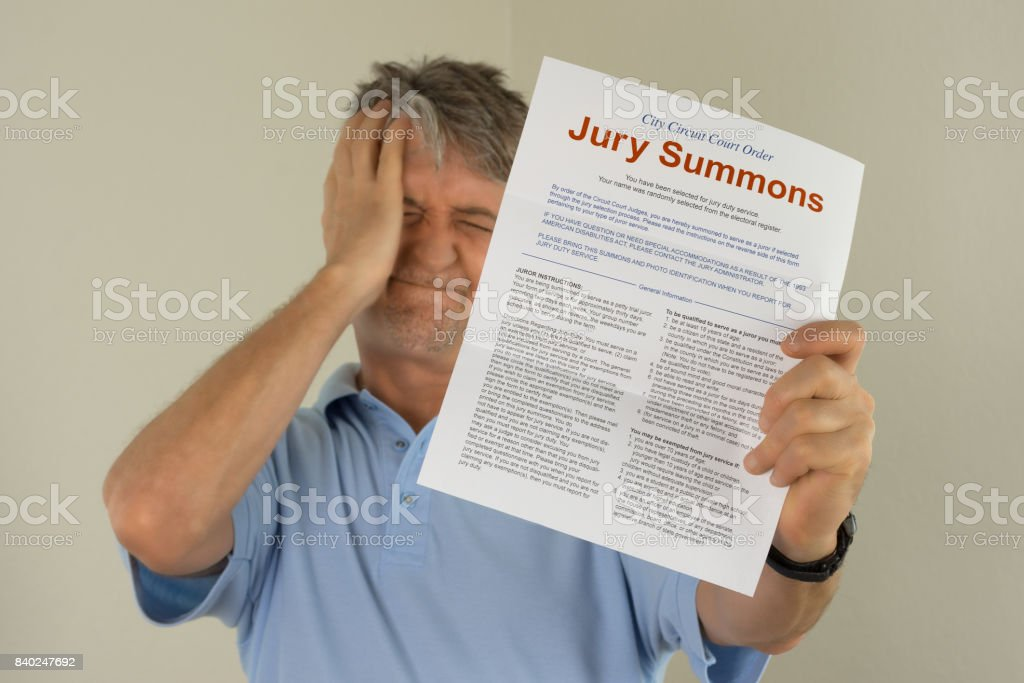 Upset man holding jury duty summons received in the mail stock photo