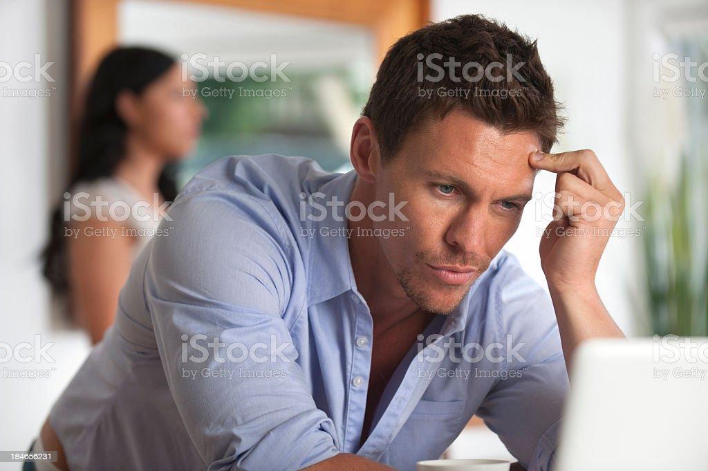 Upset man looking at a computer screen stock photo